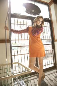 Katie Klein in orange retro dress at the laundromat for fashion photo shoot with Coco Bourgeousie